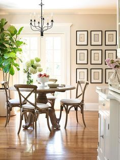 In this breakfast nook, French doors let in lots of natural light. A rustic table and bistro chairs give the space a relaxed yet upscale vibe thanks to the room's monochromatic color scheme. A simple iron chandelier pairs per