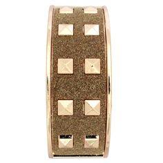 Pulseira Spikes Glitter Dourado, modelo abre e fecha é confeccionada em metal e apresenta 20 rebites de spikes e superfície texturizada com glitter.  O tamanho da pulseira é único.  É ideal para compor looks com modernidade.  dourados pequenos.o tam