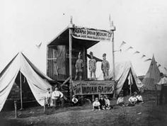 Photograph of three men dressed as Native Americans on a stage with banners advertising Kickapoo Indian Medicine Company