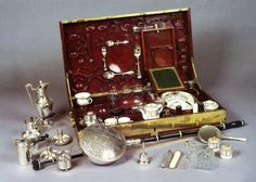 Marie Antoinette Travel Chest ~ Open view of MA's necessity travelling truck, circa 1787-1789. The big rectangular chest in veined mahogany with the corners and hinges in gilded brass, contained:  a dressing set  desk accessories  a sewing kit  glasses and bottles in cut crystal  silver cutlery  porcelain tableware  Pair of coffee cups  candle pot  sweet box  pill box  pair of glasses  thimble  small plate