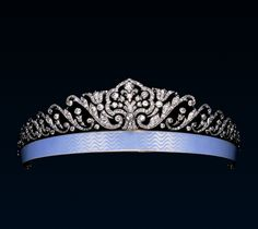 Fabergé Diamond and Blue Enamel Ribbon Tiara c1911. Diamond, platinum and gold tiara with the central floral motif within curvilinear frame flanked on each side by acanthus leaf scrolls, supported by a bandeau enamelled 'en guilloche' in an opalescent shade of pale blue. |