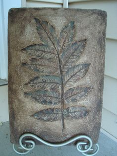 Sumac leaf pressed into vinyl cement patch, using a plastic rectangle form.