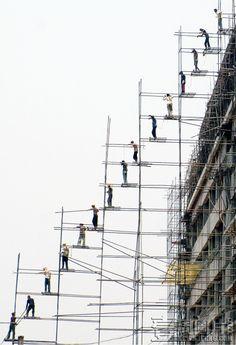 newspic:    印度一大型购物中心施工现场,15名建筑工摇摇欲坠地站在由细铁丝固定的支架上,逐一传递搭建脚手架用的木板。