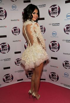 Taking her style to the next level, Selena dons a revealing cream dress. via StyleList | http://aol.it/1vaG1vh