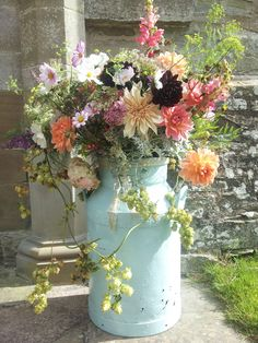 Embracing summer flower churn at church entrance by http://wildbunchflowersfromthegarden.co.uk/ Rustic wedding details