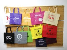 Bolsas de tela de distintos colores de fondo con impresión.