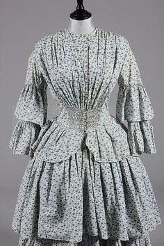 A printed cotton day dress, circa 1855, with roller-printed design of small blue flowerheads and foliage, fan pleats falling from the shoulders coverge into shirring at the front waist, flounces to sleeves and skirt, KerryTaylor Auctions