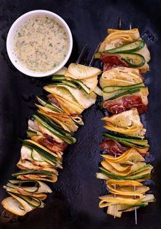 Zucchini and yellow squash ribbons and prosciutto threaded onto bamboo skewers. Brushed with olive oil and seasoned with salt & pepper.  Grilled and served with dressing of lime zest and juice, mint and garlic.and olive oil, seasoned with salt &