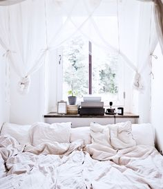 Cozy sleeping space with linen bedding and gauzy canopy