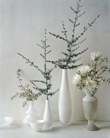 I love the centerpieces with made with cedar branches. I don't have white vases, but I think I'll to find some cheap vases of any color and spray paint them white. Also, i think you could find good branches from any pine tree and spruce them up with floral spray as in the picture.