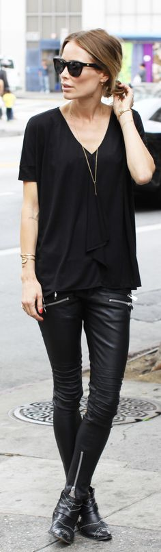Anine Bing is wearing an all black outfit, with a Dagmar top, leather trousers and ankle boots from Anine Bing
