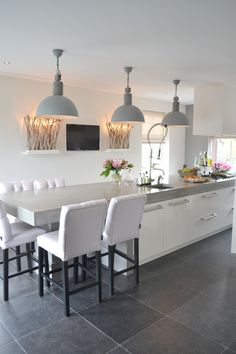 Kitchen - Contemporary kitchen with a long island & seating. Love the soft grey metal shaded pendant light fixtures....great focal point. More