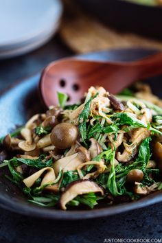 Warm Mushroom Salad with Sesame Dressing in a dark dish with wooden serving spoons.