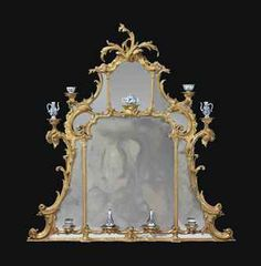 A GEORGE III GILTWOOD OVERMANTEL MIRROR CIRCA 1765 - Of shaped triangular form with an arched rectangular central plate and marginal mirrors divided by pillars and rocaille C-scrolls, surmounted by a scrolled foliate finial, the acanthus scrolled sides, central arch and apron punctuated by nine brackets, surmounted by various Kangxi blue and white porcelain wares - Dim: 60 x 56 in. (152.5 x 142.5 cm.)