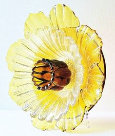 Garden flower suncatcher made from miscellaneous thrift store clear dishes. Gold bowl with amber votive holder for center.
