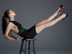Anne Hathaway showing off her core strength and long legs in a little black dress and stilettos