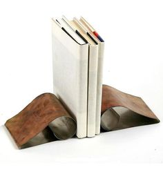 Curled Stainless Steel Bookends by Hammer It Out~ The steel is hand-cut, polished and heated for color before being bent by hand to a pleasing curled shape. And everything is polished up nicely, so you can rest easy knowing that there won't be any sharp edges interfering with your indexing and reference grabbing.  $20.00  @Sydney Hoppe by Scoutmob