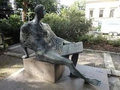 The figurative sculpture 'Sitzender lesend' (sitting man reading) was created by Fritz Nuss in 1965. It is located behind the so-called 'Wilhelmspalais' at the 'Urbanstraße' in Stuttgart, Germany, Baden-Württemberg.
