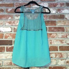 Teal Sheer Tank w/ Sequin Back Detail Sleeveless silk blouse with ornate silver sequins and beading, perfect with a white pair of pants and nude pumps! Buttans - Made in India Tops Tank Tops