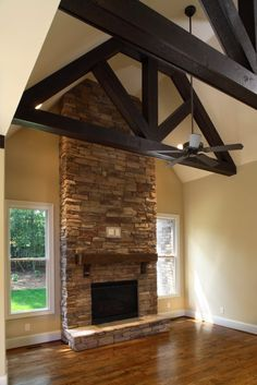 Great Room | Milestone Custom Homes | Greenville SC   Exposed wooden beams and stone fireplace bring organic elements to this modern home.