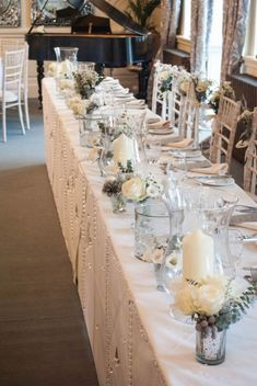 Winter wedding ideas - Top table decoration - Small vases filled with white flowers and silvery foliage - by Laurel Weddings