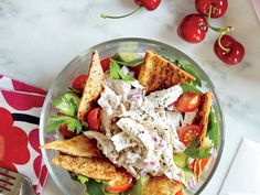 This Greek-style main dish salad features parsley salad topped with homemade chicken salad and pita chips.