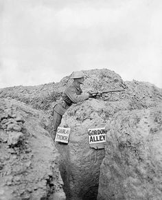 """Trenches came into widespread use in 1914 as a way for soldiers to protect themselves against the firepower of modern weaponry. Over time, they developed into huge networks. As shown here, trenches were given names to help identify them. Sometimes these names related to familiar places from home.  """"A sentry of the 10th Gordons at the junction of two trenches.  Gourlay Trench and Gordon Alley.   Martinpuich, 28 August."""""""