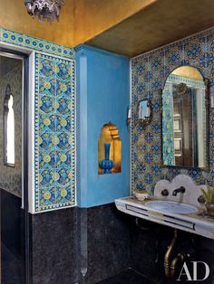 In a Los Angeles home decorated by Madeline Stuart and designed by architect Kevin A. Clark, a powder room features walls hand-painted to mimic decorative Islamic tilework. The 18th-century Italian marble sink is from Compas, and the stoneware vase and 1920s mirror are from Downtown.