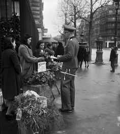 A German officer buying a bouquet featuring lily of the valley (muguet) in Paris, France on 1 May the day when the French greet each other with a small bouquet of lily of the valley, a flower that is considered a lucky charm. Pin by Paolo Marzioli 1. Mai, Occupation, Ww2 History, Photo Report, Industrial Photography, German Army, Lily Of The Valley, World War Two, Wwii