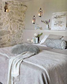 Subtile combinaison des matières pour cette chambre à l'ambiance raffinée. La douceur de la soie, de la fourrure et du linge de lit se déclinent dans un dégradé de gris pastel adoucie l'aspect brut du mur  en pierres apparentes et l'effet mat de l'enduit décoratif gris perle du mur de la tête de lit. Pour ne pas rompre l'harmonie couleurs la table de chevet est repeinte dans le même gris perle.