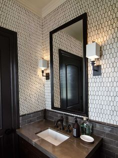 Dark trim, grey tile, greige stone, cool wallpaper do not like the way the stone vanity top cuts into door frame ?