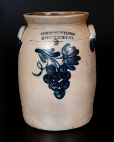 "Sold $500 Two-Gallon Stoneware Jar with Cobalt Grapes Decoration, Stamped ""COWDEN & WILCOX / HARRISBURG, PA,"" circa 1865, cylindrical jar with tooled shoulder, flared rim, and applied lug handles, decorated with a brushed design of eight grapes hanging from a stem, flanked by a looping vine and a leaf. Cobalt highlights to maker's mark, capacity mark, and handle terminals. Restoration to rim. A few shallow chips on interior of rim, two minor nicks to rim on reverse, and wear to inner rim…"