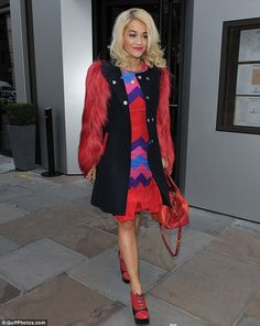Rita in a multi-coloured dress and a black coat with furry red sleeves
