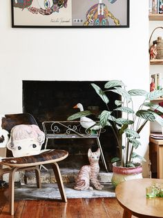 Living room detail.  Artwork above fireplace (cropped) by Keiichi Tanaami, doll cushion by Nathalie L'ete from Ganim Store, cat & pot plant ...