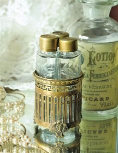 """Victorian Vanity Vials = A trio of etched glass bottles nestle together within an ornate gilded base. Once found upon dressing tables, these most commonly harboured witch hazel, mineral oil and alcohol. 4"""". VTC exclusive!   $29.95 Z"""