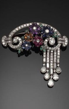 An elegant gem-set flower and diamond brooch, circa 1930, in original brown leather, gold tooled fitted case by Carrington & Co.