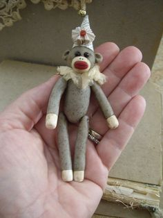 A miniature thread jointed, hand sculpted sock monkey made from polymer clay.