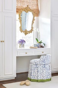 A skirted makeup stool covered in Brunschwig & Fils Les Touches fabric trimmed in green sits on a cream rug in front of a make up vanity adorning brass knobs and flanked by white wardrobe cabinets.