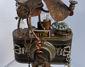 Photo Punk Dog - This art piece is made from an old camera mounted on a handmade wooden pedestal, decorated with a steampunk dog with old watch movements and parts, a 10000 lakes 1953 Minnesota License plate # 368-55, old light bulb, electronic parts, a California license tag #QBR 286, buckles, knobs, compass and dog is wearing a cap with a clock gear and camera lense has a ceramic eyeball.  #ETSY #Steampunk