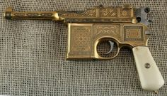 """Highly engraved and gold plated """"Bolo"""" Mauser M1896. This short barreled gun was the main production variant from 1920 to 1930, as the Treaty of Versailles prohibited Germany from making handguns with barrels longer than 100mm. The nickname comes from """"Bolshevik"""", since a large number were purchased by Soviet Russia."""