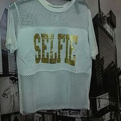 """Shirt This is a cute on the go short sleeve off white shirt.. With gold letters that spell out """"selfie"""" Very girlie.. you could pair this with sandals .espadrille shoes or some cute sneakers and you're ready to go!! Tops Tees - Short Sleeve"""