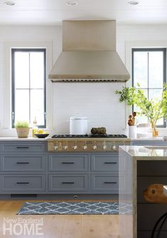 The kitchen's oversize drawer pulls match the assertiveness of the black window frames.