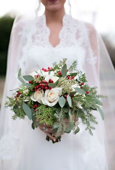 Pretty Christmas wedding bouquet, white roses, winter greenery, red berries