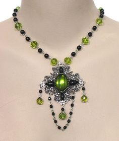 A pretty vintage West German glass olivine jewel is the focal point for this one of a kind necklace.  I also used olivine glass beads, vintage jet glass beads and vintage jet glass jewels.  An ornate backing of silver & gunmetal filigree evokes the spirit of Renaissance style adornment. The centerpiece measures 3 1\/2 long including the chain drape.  The beaded chain adjusts from 15-19 long. Custom sizing is free