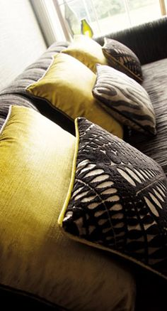 citrine and dark grey pillows on a grey sofa.  dark grey pillows feature a great textured design, cut away to reveal a lighter color below