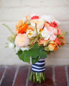 Buquê de noiva com peônias rosa claro, laranja, salmão. Fita listrada em preto e branco.