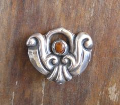 """Knud Georg Jensen. Skonvirke silver and carnelian brooch.  Marks KGJ (partial), 830S and D - Hammer - A"""" for Dansk Arbedje, trade association for promoting Danish product. Repoussé.  View 1."""