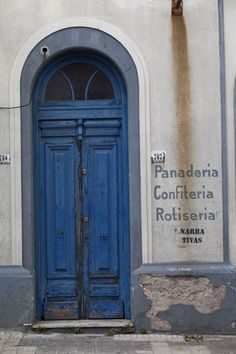 Photograph of Old wooden door with signs on the wall in the old centre of Montevideo - Uruguay -South America