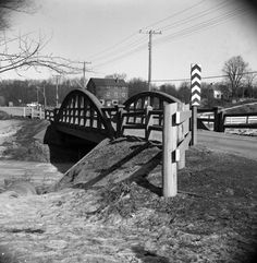 Fish Mill, Bayview bridge -- Photo credit Ted Chirnside -- Lot 25, Con. 1 east. Looking north-east up Bayview Avenue towards Steeles Avenue, across bridge over East Don River. Taken from the Mazo de la Roche property. The Fish Mill is visible on the north-east corner of the intersection. This mill was built around 1830 by Benjamin Fish and later owned by Charles Parsons (1866), James Reith (1878), H. B. Schmidt (1883), W. H. Lever (1920), and finally Angus A. Macdonald (1938), who was an…