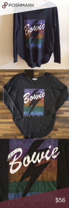 "Junk Food Bowie Graphic Tee Rock & Roll Junk Food Clothing David Bowie! Super soft and comfy, vintage inspired long sleeve graphic tee. Color is a little off black with distressed graphic, to give it that vintage vibe. Came this way from manufacturer. Rounded shirttail hem.   50% cotton 50% modal.   Women's small.  Front length approx 26"" Back length approx 29"" Bust when laid flat approx 21"" Measurements are approximate within one inch.  Worn once for an hour, excellent condition. Junk Food…"
